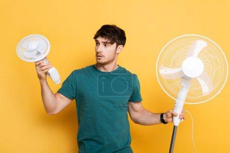 Photo pour Jeune homme frustré tenant avec deux ventilateurs électriques sur jaune - image libre de droit