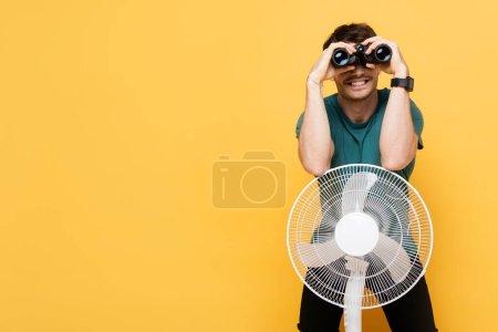 Photo pour Homme joyeux regardant à travers les jumelles tout en se tenant debout avec ventilateur électrique sur jaune - image libre de droit