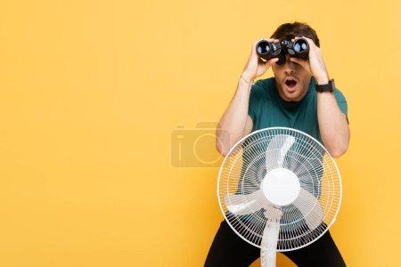 Photo pour Homme choqué regardant à travers les jumelles tout en se tenant debout avec ventilateur électrique sur jaune - image libre de droit