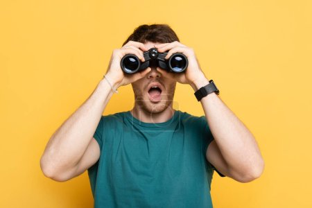 young shocked man looking through binoculars on yellow