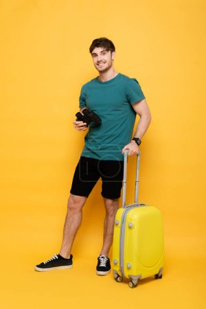 Photo for Happy man with suitcase and binoculars ready for summer vacation on yellow - Royalty Free Image