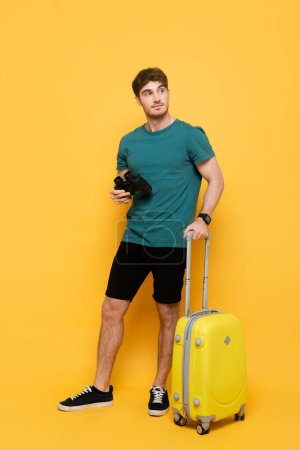 Photo for Handsome man with suitcase and binoculars ready for summer vacation on yellow - Royalty Free Image