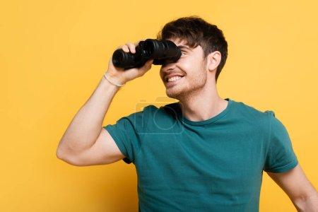 handsome smiling man looking through binoculars on yellow