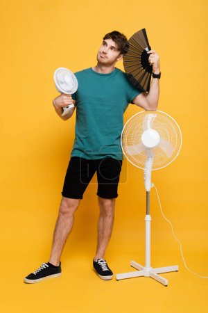Photo for Handsome man suffering from heat with two electric fans and hand fan on yellow - Royalty Free Image