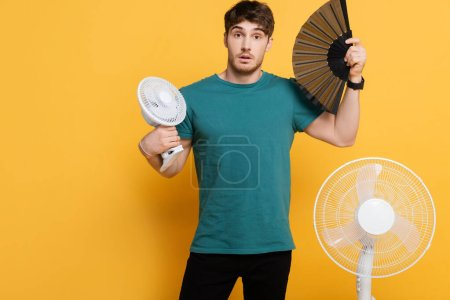 Photo for Young man suffering from heat with two electric fans and hand fan on yellow - Royalty Free Image
