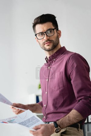 young, serious businessman in eyeglasses looking away while holding documents