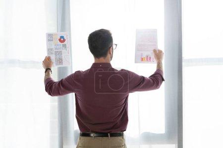 Photo pour Vue arrière de l'homme d'affaires regardant des documents tout en se tenant près de la fenêtre - image libre de droit