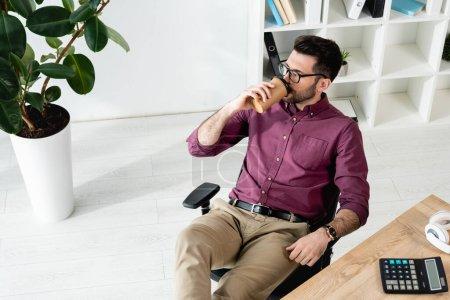 Photo pour Vue grand angle de jeune homme d'affaires buvant du café pour aller tout en étant assis sur le lieu de travail près de l'usine en pot - image libre de droit