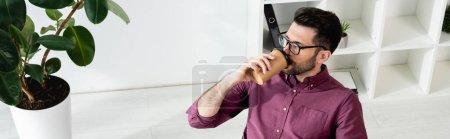 Photo pour Vue grand angle de jeune homme d'affaires buvant du café pour aller près de la plante en pot, concept horizontal - image libre de droit