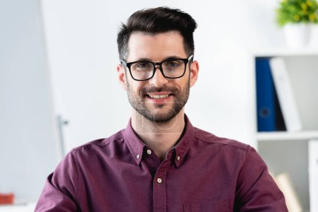 happy, handsome businessman in eyeglasses smiling while looking at camera