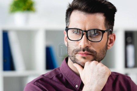 Photo pour Confiant, homme d'affaires coûteux dans les lunettes toucher le menton tout en détournant les yeux - image libre de droit