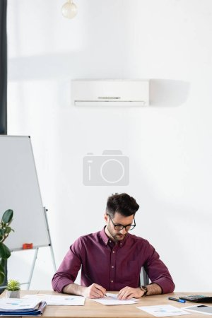 Photo for Attentive businessman writing on paper near flipchart while sitting under air conditioner - Royalty Free Image