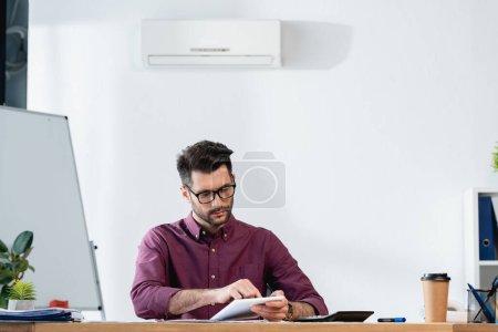 Photo pour Bel homme d'affaires utilisant tablette numérique tout en étant assis sur le lieu de travail sous climatiseur sur le mur - image libre de droit