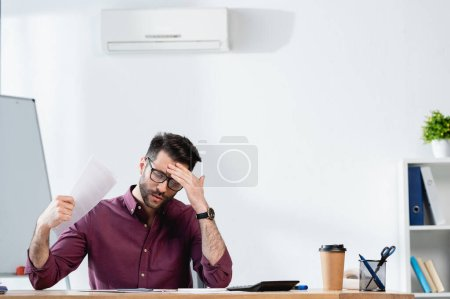 Photo for Exhausted businessman touching forehead and waving paper while suffering from heat in office - Royalty Free Image