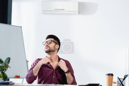 Photo for Exhausted businessman sitting at workplace and touching shirt while suffering from heat in office - Royalty Free Image
