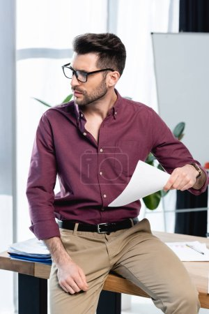 exhausted businessman sitting on desk and waving paper while suffering from heat in office