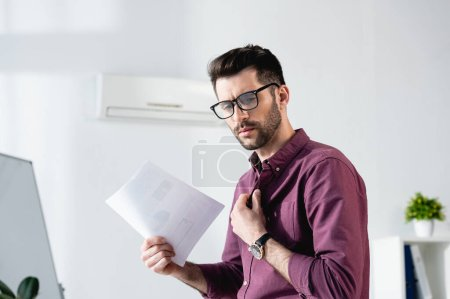 Photo for Displeased businessman waving paper and touching shirt while suffering from heat in office - Royalty Free Image