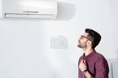 Photo pour Jeune homme d'affaires regardant climatiseur tout en touchant chemise et souffrant de chaleur - image libre de droit