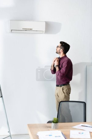 Photo for Young businessman touching shirt while standing under air conditioner and suffering from heat - Royalty Free Image