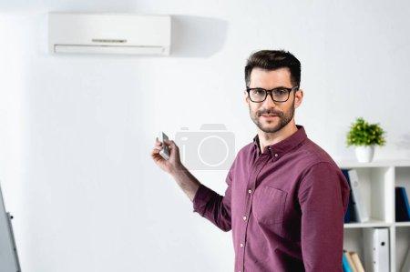 Photo pour Homme d'affaires heureux souriant à la caméra tout en allumant le climatiseur avec télécommande - image libre de droit