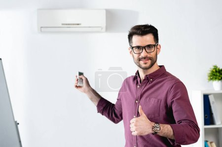Photo for Smiling businessman showing thumb up while switching on air conditioner with remote controller - Royalty Free Image