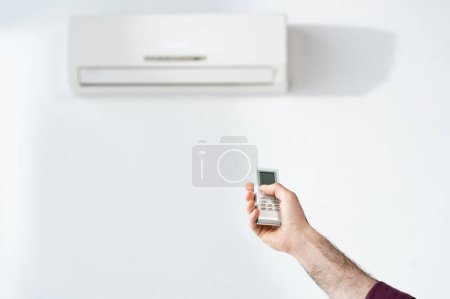cropped view of businessman switching on air conditioner in office with remote controller