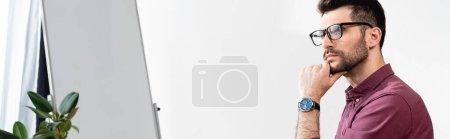 Photo pour Image horizontale d'un homme d'affaires réfléchi en lunettes touchant le menton et regardant loin près du tableau à feuilles mobiles - image libre de droit