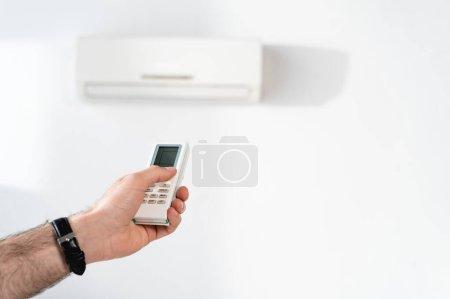 Photo pour Vue recadrée de l'homme d'affaires commutation sur climatiseur avec télécommande - image libre de droit