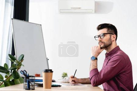Photo pour Homme d'affaires réfléchi toucher le menton, détourner les yeux et tenant crayon tout en travaillant près du climatiseur sur le mur - image libre de droit