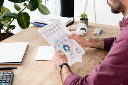 Photo pour Vue recadrée d'un homme d'affaires tenant du papier avec analytique près d'un ordinateur portable et d'écouteurs sans fil - image libre de droit