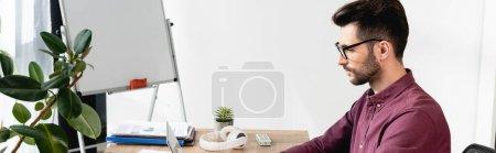 Photo pour Orientation panoramique du jeune homme d'affaires sérieux assis sur le lieu de travail près de tableau à feuilles mobiles et usine verte - image libre de droit