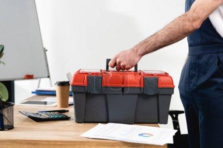 Photo pour Vue recadrée du réparateur avec boîte à outils sur bureau avec papiers et café à emporter - image libre de droit