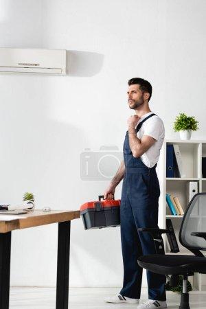 Photo pour Beau réparateur debout avec boîte à outils près de climatiseur cassé et souffrant de chaleur - image libre de droit