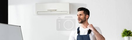 Photo pour Récolte panoramique de réparateur debout avec boîte à outils près de climatiseur cassé et souffrant de chaleur - image libre de droit