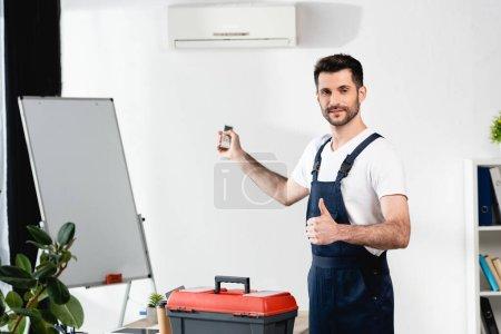 Photo pour Travailleur souriant tenant télécommande et montrant pouce vers le haut tout en se tenant près de la boîte à outils et climatiseur - image libre de droit