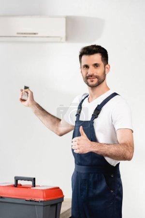 Photo pour Réparateur souriant tenant télécommande et montrant pouce près de la boîte à outils et climatiseur sur le mur - image libre de droit