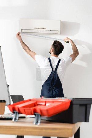 Photo pour Foyer sélectif du réparateur mesurant climatiseur près du bureau bureau avec boîte à outils - image libre de droit