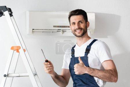 Photo pour Réparateur heureux montrant pouce vers le haut et tenant tournevis tout en se tenant près escabeau et climatiseur - image libre de droit