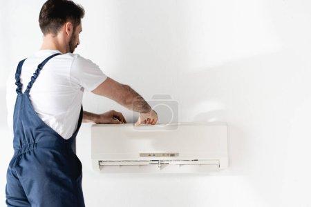 Photo pour Réparateur en salopette fixation climatiseur sur mur blanc - image libre de droit