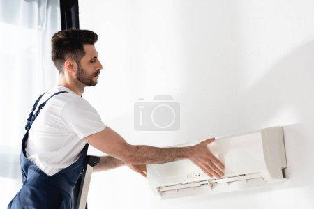 Photo pour Jeune réparateur ouverture climatiseur fixé sur tout mur - image libre de droit