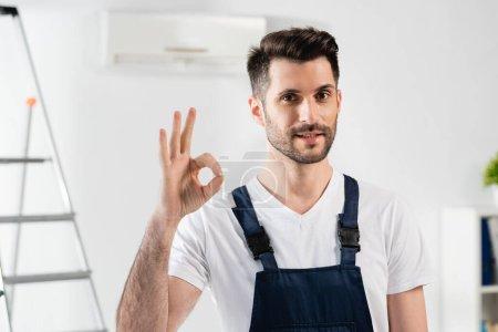 Photo pour Réparateur souriant montrant un geste correct tout en se tenant près de l'escabeau et climatiseur sur le mur - image libre de droit