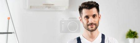 Photo pour Image horizontale du beau réparateur souriant regardant la caméra près du climatiseur sur le mur - image libre de droit