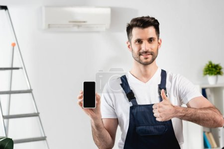 smiling repairman holding smartphone with blank screen and showing thumb up