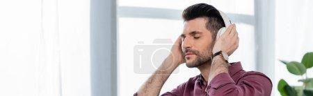 horizontal image of dreamy businessman listening music in wireless headphones in office