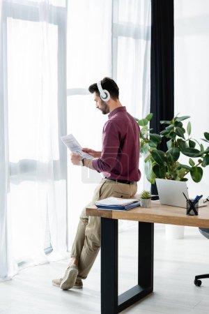 Photo pour Homme d'affaires dans un casque sans fil regardant le document tout en étant assis sur le bureau près de la fenêtre - image libre de droit