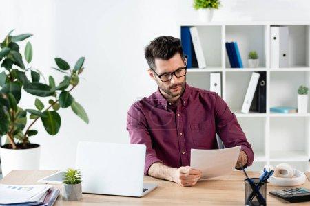 Photo pour Homme d'affaires attentif regardant le document tout en étant assis sur le lieu de travail près d'un ordinateur portable - image libre de droit