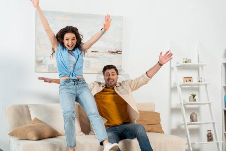 Cheerful couple with raised hands looking at camera in living room
