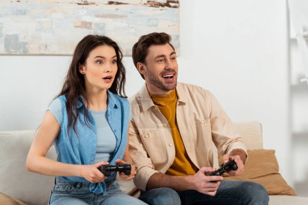 Photo for KYIV, UKRAINE - JUNE 4, 2020: Shocked woman playing video game near smiling boyfriend at home - Royalty Free Image