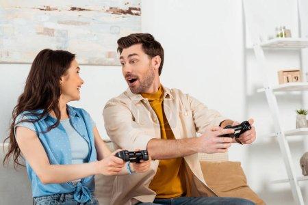 Photo pour KYIV, UKRAINE - 4 JUIN 2020 : Homme excité jouant à un jeu vidéo avec une petite amie souriante dans le salon - image libre de droit
