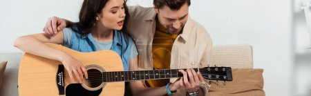 Photo for Panoramic shot of man teaching girlfriend to playing acoustic guitar - Royalty Free Image